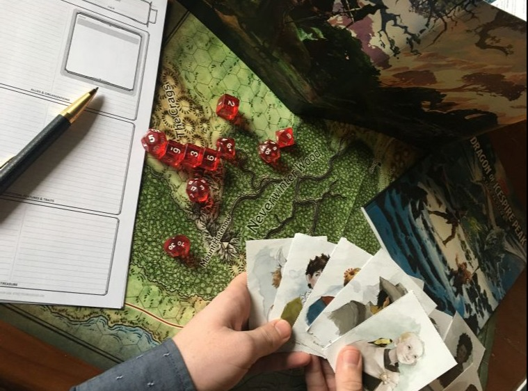 Person playing Dungeons and Dragons, focus on hands, board and cards with notepad and pen for scoring